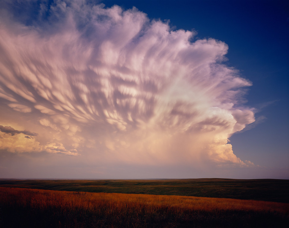 Cheyenne River Sioux Tribal Park with severe storm clouds at sunset amid vast grassland. Montana.