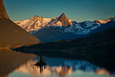 Morning light brightens the peaks above the St. Mary valley. The peaks are reflected into St. Mary Lake. Wild Goose Island is a famous point in the lake.  Photo by Kyle Spradley | www.kspradleyphoto.com