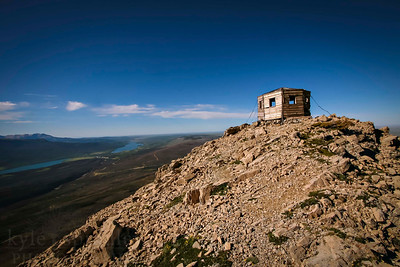 An old wooden shelter stands on a cliff edge overlooking the St. Mary valley from atop the peak of Divide Mountain.  Photo by Kyle Spradley | www.kspradleyphoto.com
