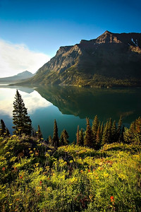 In the morning light, peaks are reflected in St. Mary Lake.  Photo by Kyle Spradley | www.kspradleyphoto.com