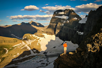 A hiker looks down at Grinnel Glacier from the overlook off the Highline Trail in the late afternoon hours. The trail is one of the many favorited by hikers who visit Glacier National Park in Montana.  Photo by Kyle Spradley | www.kspradleyphoto.com