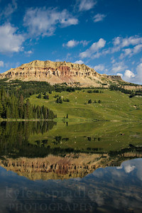 Peaks above Beartooth Lake are reflected just off the road through the Beartooth Pass.   Photo by Kyle Spradley | www.kspradleyphoto.com