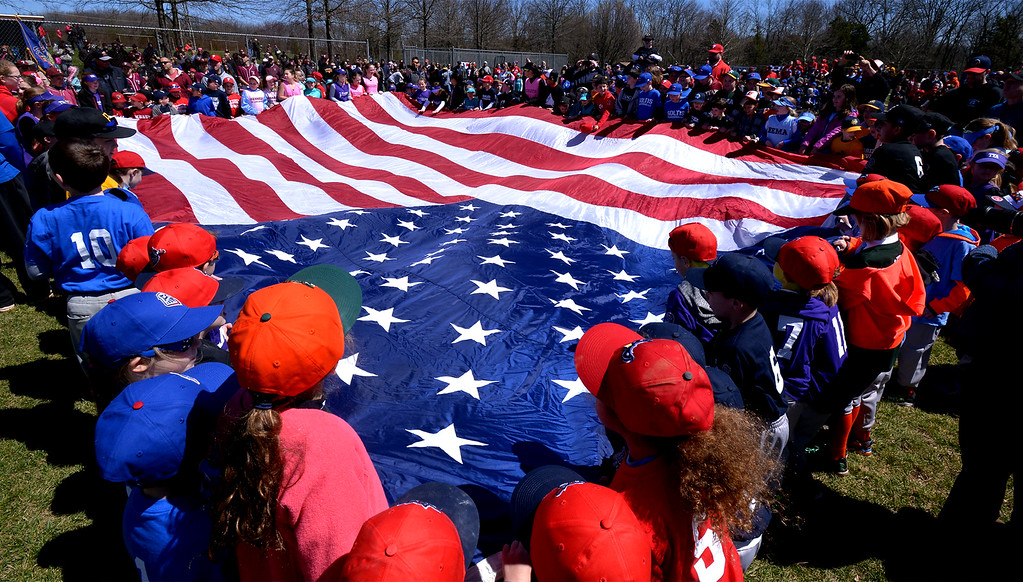 . (Bob Raines--Digital First Media)___ Players stretch out a huge American flag on opening day of the Hatfield-Towamencin Little League season April 8, 2017.