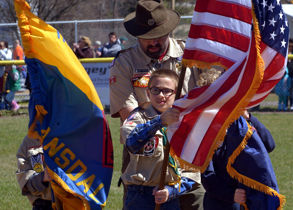 . (Bob Raines--Digital First Media)___ Cub Scouts and Boys Scouts in the color guard have a hard time keeping the colors under control in the cold gusty wind on North Penn Little League Opening Day April 8, 2017.