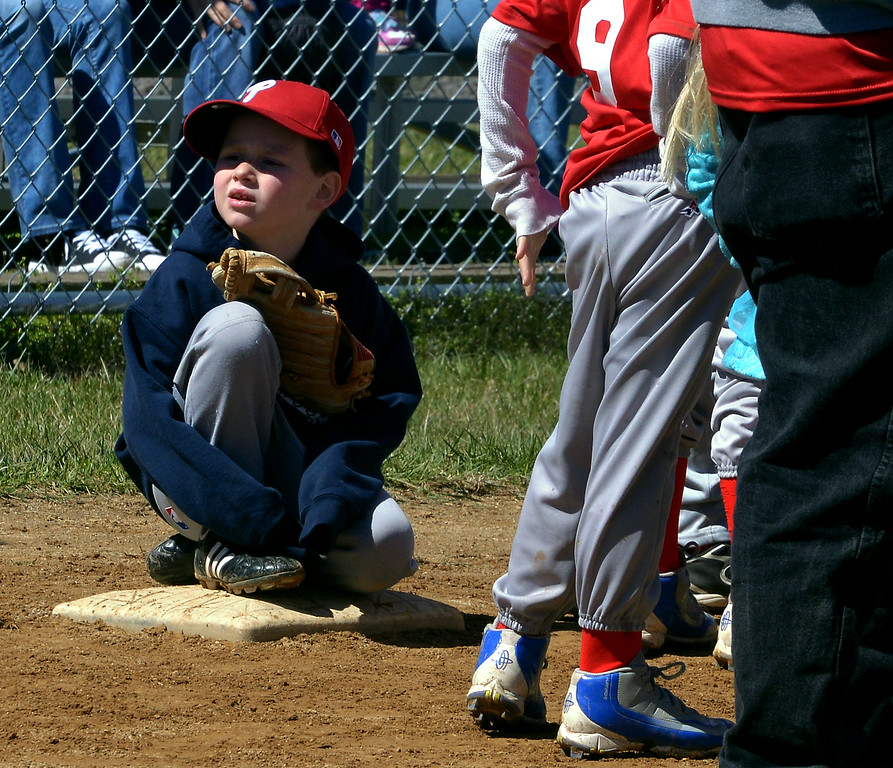 . (Bob Raines--Digital First Media)___ A little leaguer shivers in his hoodie crouched on first base waiting for the North Penn Little League Opening Day festivities to begin on a chilly April 8, 2017.