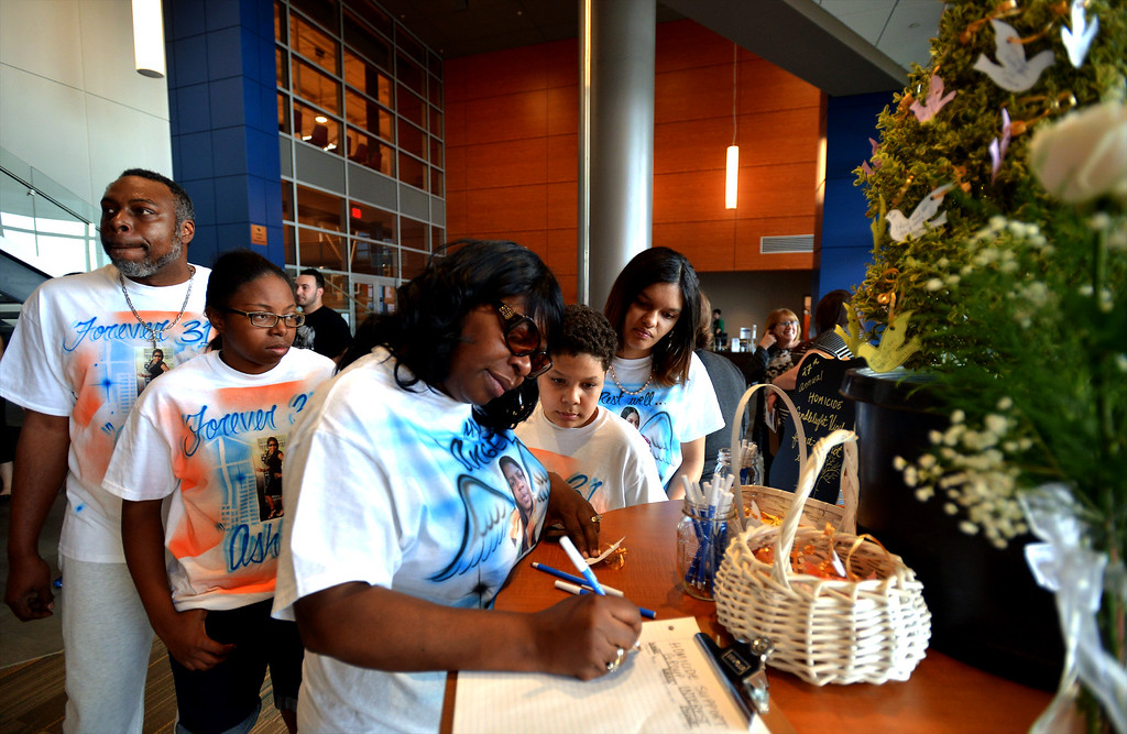 . Her family surrounds Lula Conway as she writes a note to her daughter, Ashley, a victim of violence, to place on a tree of remembrances at the Victim Services Center Annual Candlelight Vigil April 11, 2017.  (Bob Raines--Digital First Media)