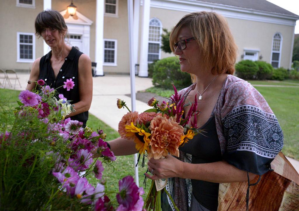 . Leslie Jones, right, buys cut flowers from grower, Cathy Olsen, Nurturing Nature Flowers, at the Hatboro Farmers Market Aug. 18, 2017. / Bob Raines--Digital First Media