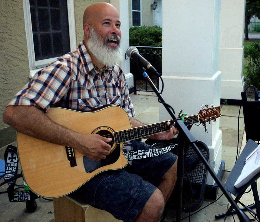 . Entertainer Leo Ricobaldi keeps an eye on a rapidly approaching thunderstorm to gauge how long he could sing before he had to pack his gear and get under cover at the Hatboro Farmers Market Aug. 18, 2017. / Bob Raines--Digital First Media