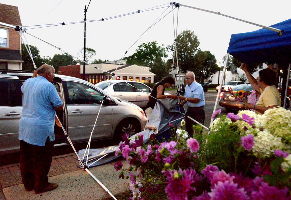 . Nurturing Nature Farm grower Cathy Olsen, center, gets help taking apart her broken canopy after high winds preceding an afternoon thunder storm overturned it, as well as several others at the Hatboro Farmers Market Aug. 18, 2017. / Bob Raines--Digital First Media