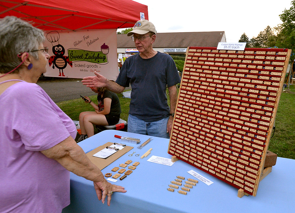 . Bob DeVore, owner of Creative Woodworking, speaks with Anita Wendler about his hand carved name tags at the Hatboro Farmers Market Aug. 18, 2017. / Bob Raines--Digital First Media