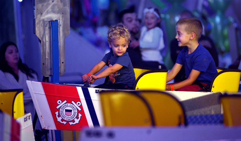 . George, left, and Charlie Dziedzic ride in a Coast Guard boat at the Upper Gwynedd Township Carnival Sept. 7, 2017. / Bob Raines--Digital First Media