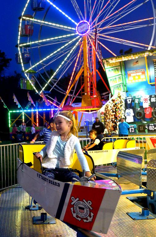. Sierra Jaffe pilots a Coast Guard boat on a carousel at the Upper Gwynedd Township Carnival Sept. 7, 2017. / Bob Raines--Digital First Media