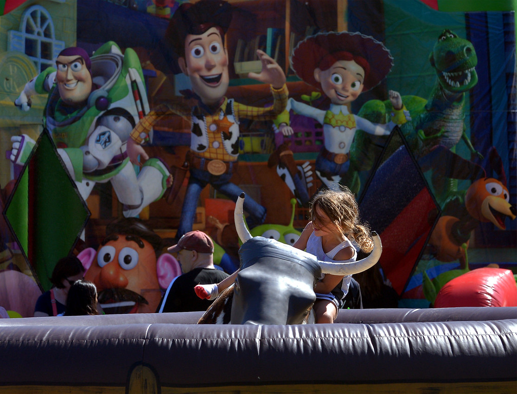 ". ""Toy Story\"" characters painted on an inflatable ride appear to be cheering for the girl riding mechanical bull with at the Whitpain Community Festival Sept. 23, 2017. / Bob Raines--Digital First Media"