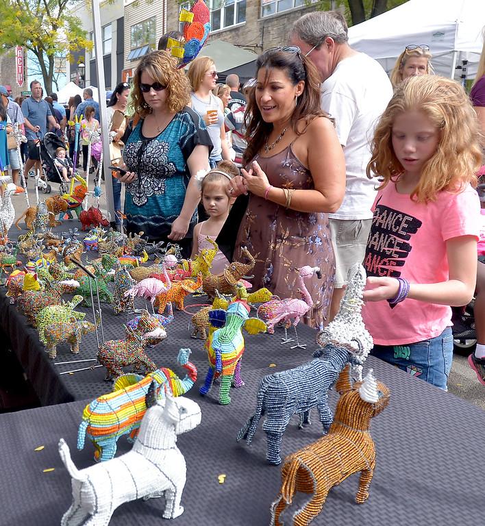 . Browsers look at beaded animal figurines during Ambler\'s Oktoberfest Oct. 7, 2017. / Bob Raines--Digital First Media