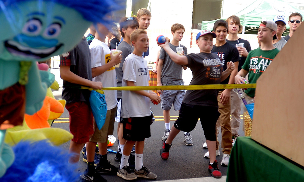 . Boys try to topple a pile of cans to win a prize at the Ambler Oktoberfest Oct. 7, 2017. / Bob Raines--Digital First Media