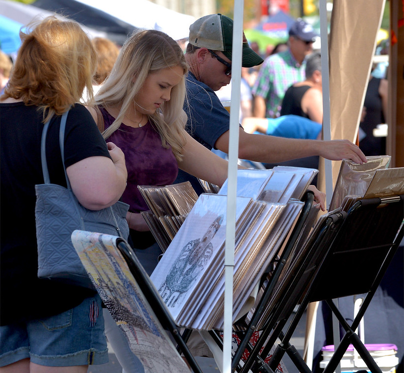 . Oktoberfest visitors look through the art work at the Philly Word Art booth in Ambler  Oct. 7, 2017. / Bob Raines--Digital First Media