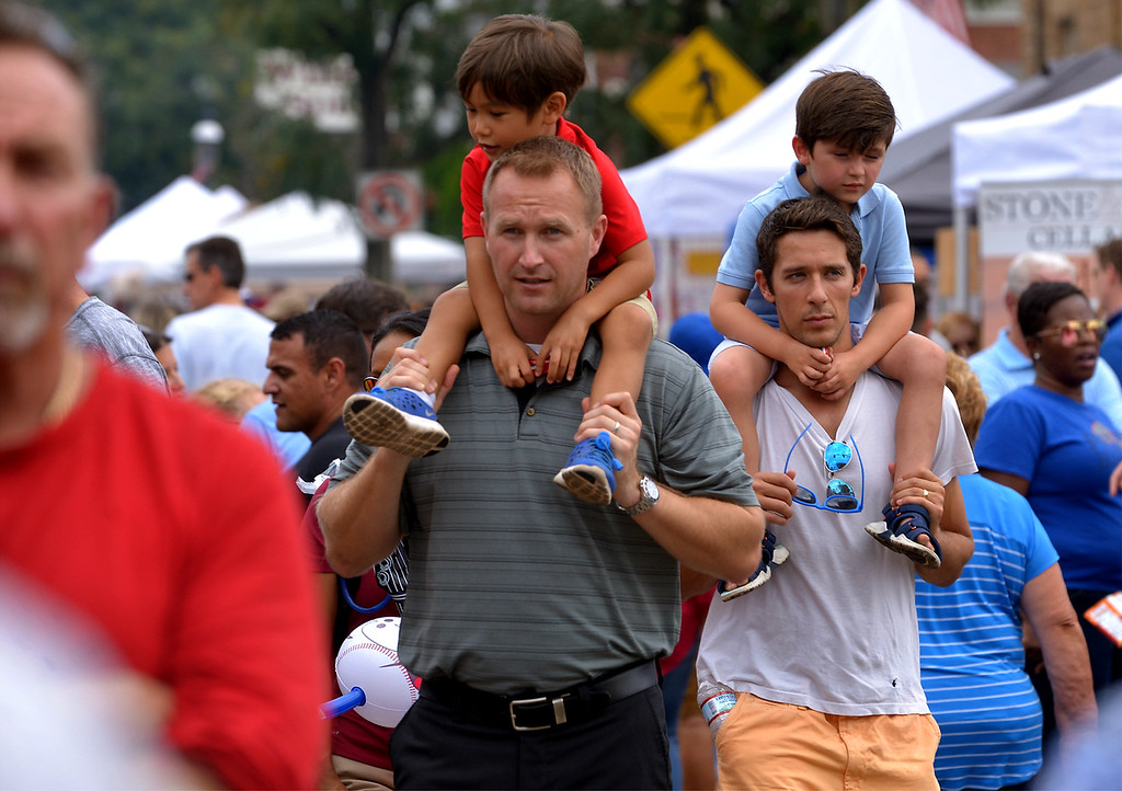 . A pair of fathers provide their sons an elevated view as they cruise along Butler Ave. at the Ambler Oktoberfest Oct. 7, 2017. / Bob Raines--Digital First Media