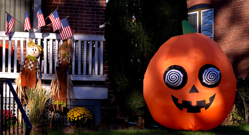 . A blow-up pumpkin with hypnotic eyes and smiling scarecrows decorate the front of a house in Lansdale Oct 27, 2017. (Bob Raines--Digital First Media)