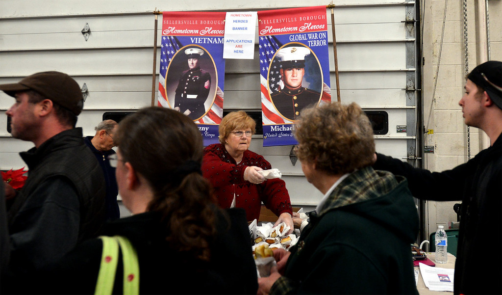 . Judy Potoczny, center, hands out soft pretzels at the Hometown Heroes table during the Sellersville Fire Company Winterfest Dec. 5, 2017. (Bob Raines--Digital First Media)
