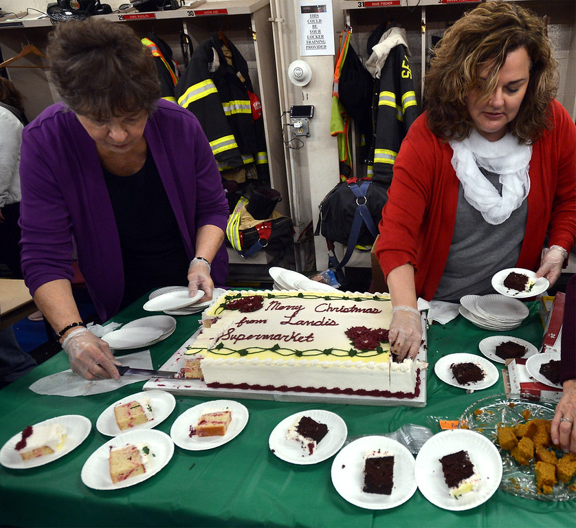 . Eileen Brothers, left, and Erin Landis set out pieces of the Landis Supermarket Christmas cake at the Sellersville Fire Company Winterfest Dec. 5, 2017. (Bob Raines--Digital First Media)