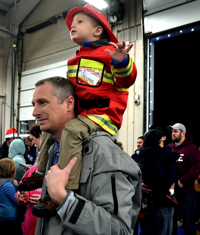 . Andrew McCaskill holds his son, Grayson McCaskill, on his shoulders as they wait to visit Santa at the Sellersville Fire Company Winterfest Dec. 5, 2017. (Bob Raines--Digital First Media)