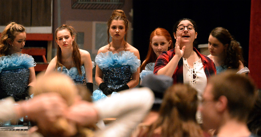 ". Music director Jen Buono, right, instructs the ensemble cast of ""Little Shop of Horrors\"" to sing strongly through the entire song and not trail off at the end of a line. The Young Starrs Theater Company production runs Dec. 9, 10 and 11 in the Temple University Ambler Campus auditorium.   