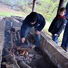 As the day's temperatures dip and snow falls, derby organizers stoke the fire to keep warm. Debby High — Digital First Media