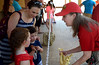 Kathleen McNamee, right, shows a cast of a giraffe's jaw to Andrea Raynor and her children, Connor and Charlotte as they wait in line to feed Dhoruba at the Giraffe Welcome Home Party at the Elmwood Zoo, May 28, 2016.   / BOB RAINES--DIGITAL FIRST MEDIA