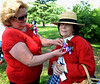 Ella Aderman, president of the Historical Society of Montgomery County, left, pins a corsage on board member Paula Gidjunis who is in period dress for the Memorial Day observation at Montgomery Cemetery May 28, 2016. / BOB RAINES--DIGITAL FIRST MEDIA