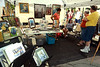 Nicole Snider, seated, talks to shoppers about her work at the Ambler Art and Music Festival June 18, 2016. __ BOB RAINES-- DIGITAL FIRST MEDIA