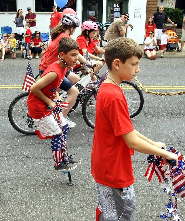 . Decorated bicycles, a scooter, and a pogo stick make their way along Main St. during the North Wales Independence Day Parade July 4, 2016. _ Bob Raines | Digital First Media