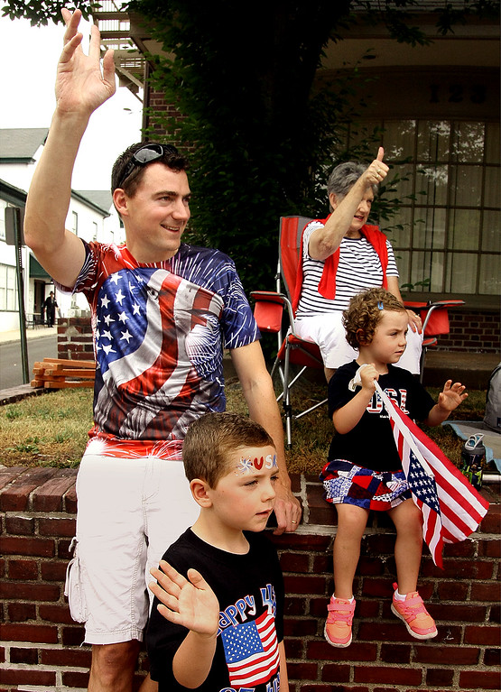 . Andrew Burke, his children, Patrick and Millie, and his mother, Marcia Burke, wave during the North Wales Independence Day Parade July 4, 2016. They are originally from Australia. _ Bob Raines | Digital First Media