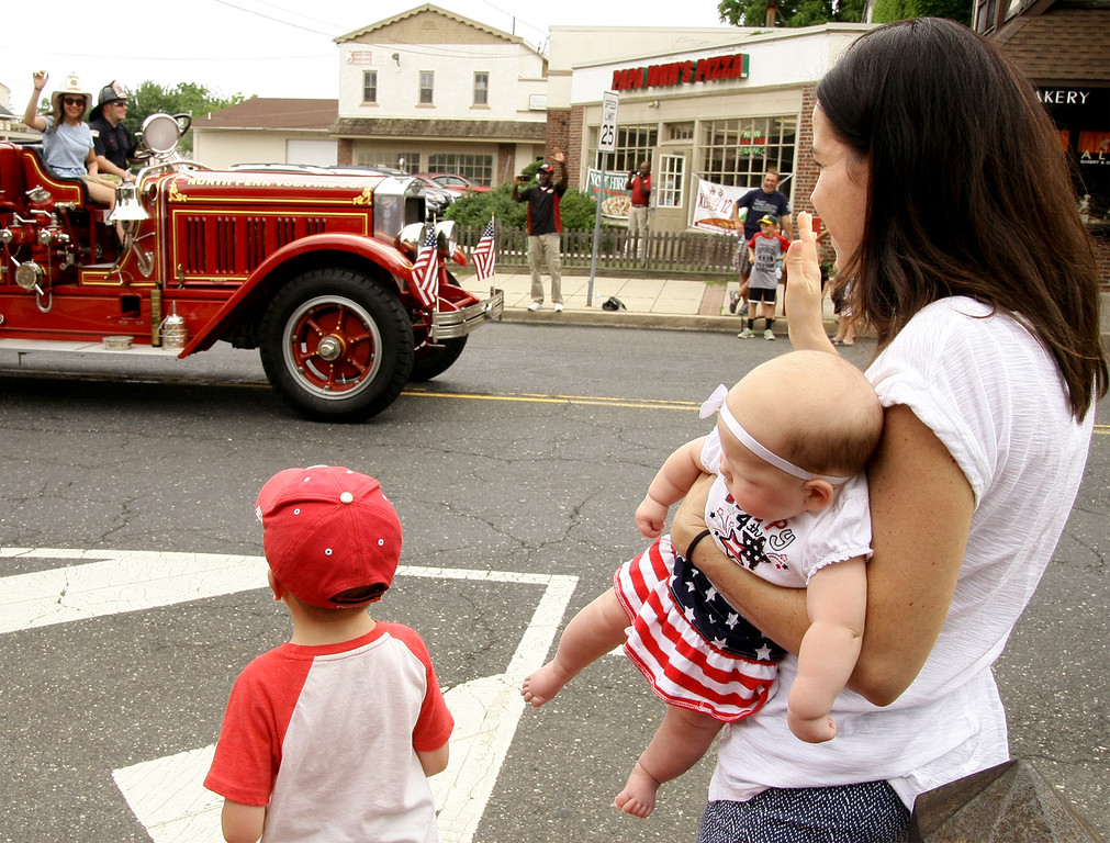 . Bridget Dombrowski holds three-month-old Anna Gruver while Anna\'s mother watches  her other children collecting candy from Main St. at the North Wales Independence Day Parade July 4, 2016. _ Bob Raines | Digital First Media