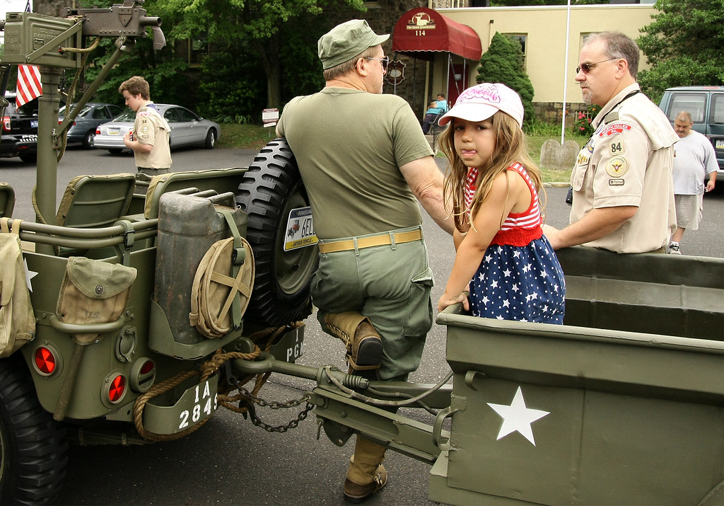 . Elizabeth Cherry waits patiently for the North Wales Independence Day Parade to start as her grandfather, Dale Cherry, left, and Dave Arnold, a scout leader from Boy Scout Troop 84 talk July 4, 2016. _ Bob Raines | Digital First Media