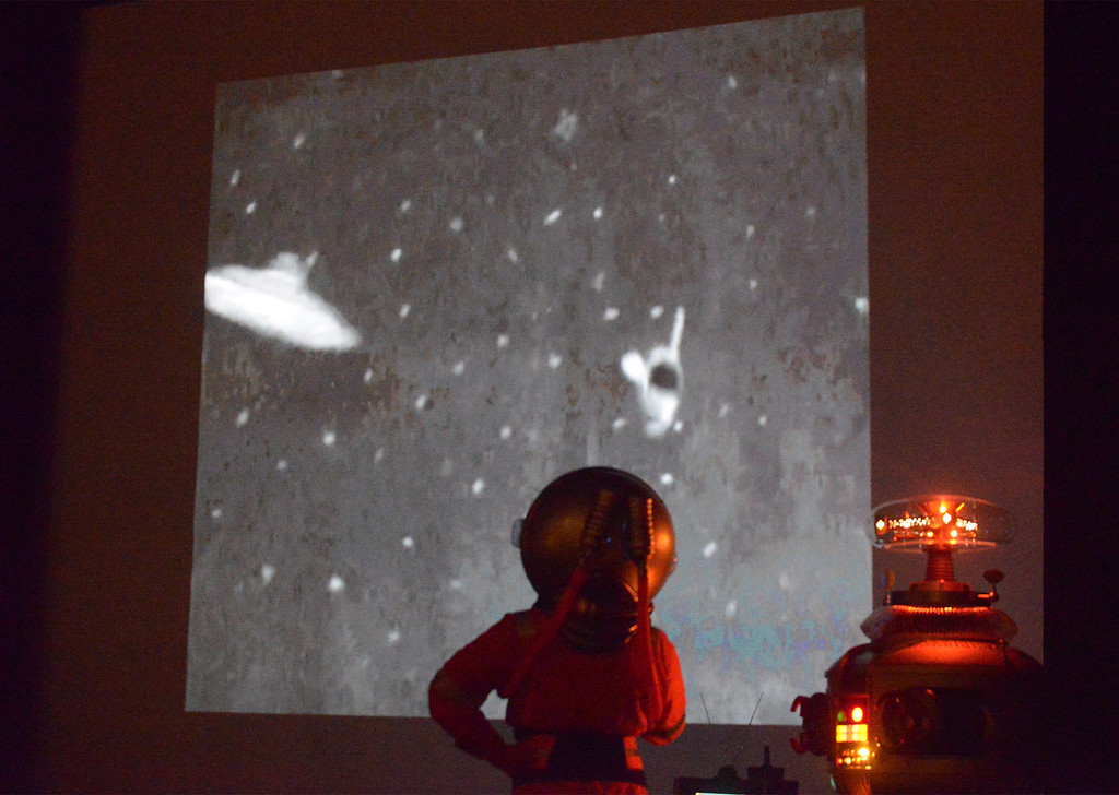 """. Mr. Lobo, in his spacesuit, left, and B-9 Robot watch a clip from Lobo\'s remake of Ed Wood\'s \""""Plan 9 from Outer Space\"""" at Blobfest July 8, 2016. _ Bob Raines 