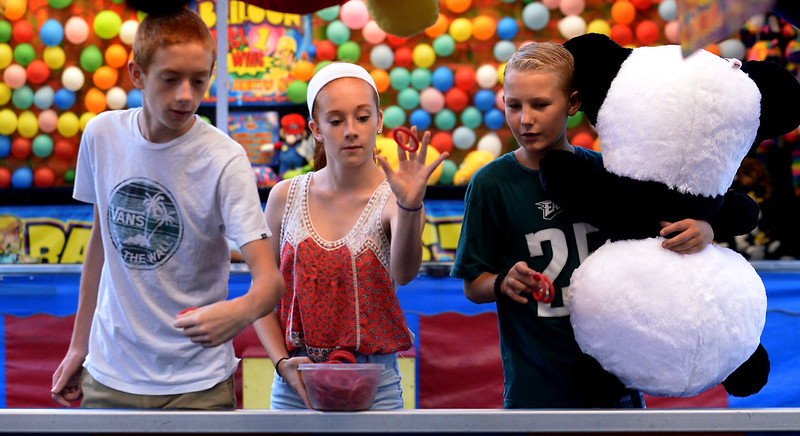 Kole Sonsteby, right, watches Nathaniel and Liz Gangi toss rings trying to win a prize at Annual Sellersville Fire Department Carnival July 13, 2016. _ Bob Raines | Digital First Media