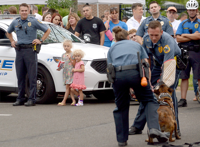 Two little girls stand close together next to a policeman as they watch a demonstration by the Horsham Police K-9 Unit at the Horsham Night Out Aug. 2, 2016. / BOB RAINES--DIGITAL FIRST MEDIA