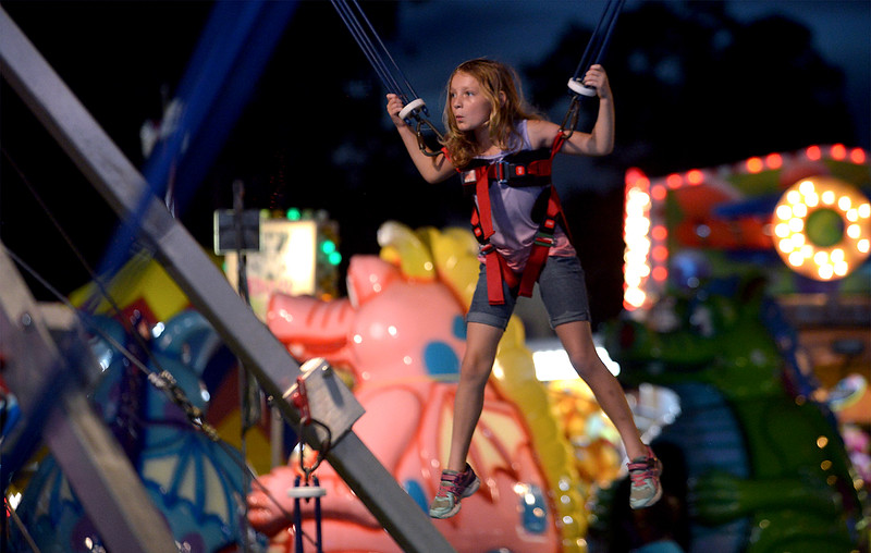 A  girl bounces up and down while tethered to bungee cords at the Dublin Firemen's Fair Aug. 12, 2016.  |  BOB RAINES--DIGITAL FIRST MEDIA