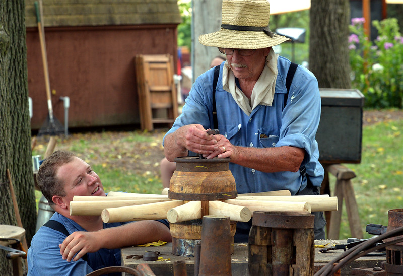 Blake Bardman, left, and Dean LaBar assemble a wagon wheel at the Goschenhoppen Folk Festival Aug. 12, 2016.  |  BOB RAINES--DIGITAL FIRST MEDIA