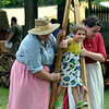 Helen Spadis, left, and Brianna Maurer help a little girl walk on stilts at the Goschenhoppen Folk Festival Aug. 12, 2016.  |  BOB RAINES--DIGITAL FIRST MEDIA