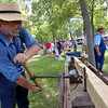 Frank Horst uses an auger to bore holes in a fence post at the Goschenhoppen Folk Festival Aug. 12, 2016.  |  BOB RAINES--DIGITAL FIRST MEDIA