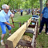 Frank Horst, right, lets Arcady Kolpakov take a turn boring holes in a fence post with an auger at the Goschenhoppen Folk Festival Aug. 12, 2016.  |  BOB RAINES--DIGITAL FIRST MEDIA
