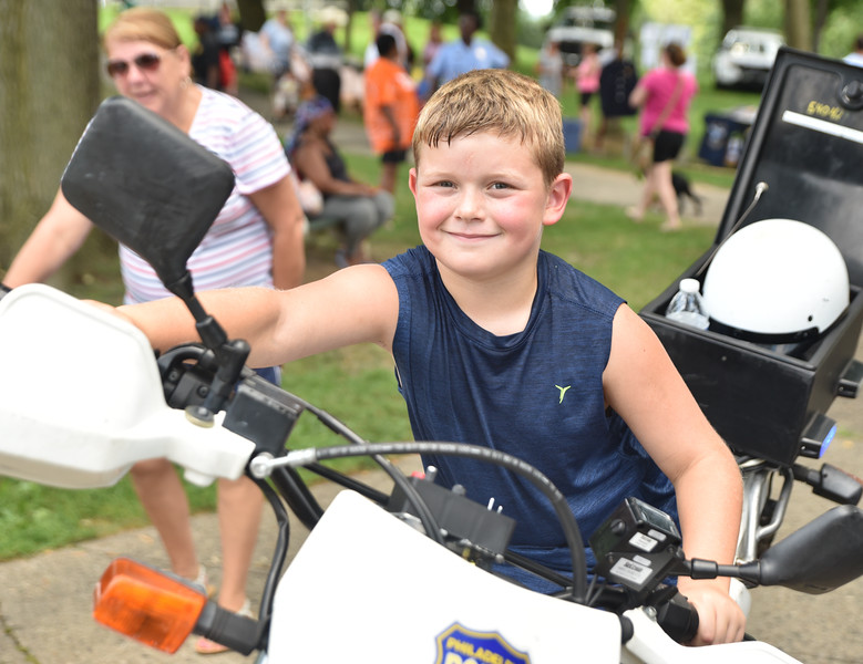 Riley Rumsey sits on a police motorcycle during the Fifth Police District's Community Day at Gorgas Park Aug. 13.  Rick Cawley — For Digital First Media