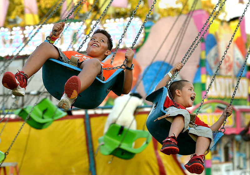 Two boys have fun on the swing carousel at the Upper Gwynedd Carnival Sept. 8, 2016.  (Bob Raines--Digital First Media)