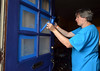 Bob Raines--Digital First Media <br /> Donna Birdsell removes painters tape from a newly painteddoor on Swede St, Norristown during the Rock the Block community improvement event Sept. 17, 2016.