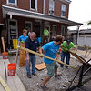 (Bob Raines--Digital First Media)    <br /> Volunteers make a temporary plywood and lumber walkway to bridge area where they dug out a concrete slab in front of a Habitat for Humanity property on Basin St., Norristown, during the Rock the Block community improvement event Sept. 17, 2016.