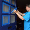 (Bob Raines--Digital First Media)    <br /> Donna Birdsell removes painters tape from a newly painted door on Swede St, Norristown during the Rock the Block community improvement event Sept. 17, 2016.