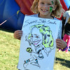Brooke Linck, 7, holds a caricature of herself playing her favorite sport, soccer, at the 2016 SeptemberFest in James Memorial Park in West Rockhill Sunday, Sept. 25.  Debby High — For Digital First Media