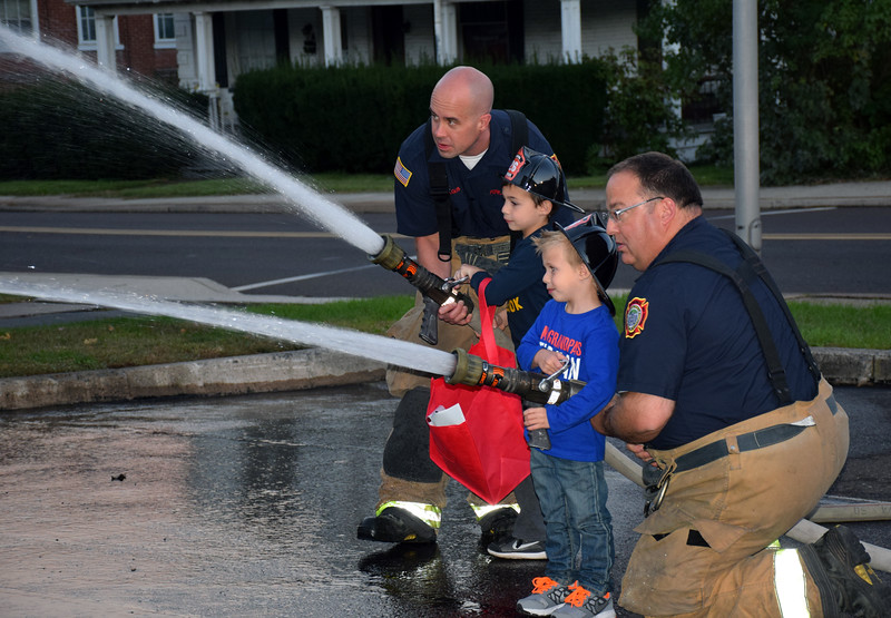 Firefighters help children learn how to use a firehose during the Perkasie Fire Company's open house Thursday, Oct. 13.  Debby High — For Digital First Media