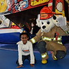 Isaac Shumburo meets Sparkey after he ran through the firetruck playhouse at the Sellersville Fire Department's annual open house event Saturday, Oct. 22.  Debby High — For Digital First Media